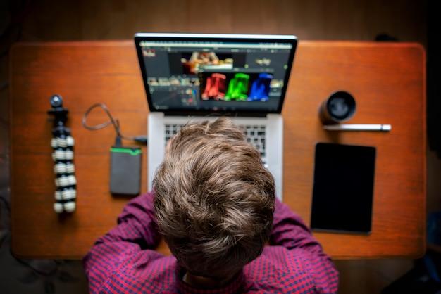 De mannelijke producent bewerkt video op zijn laptop in studio