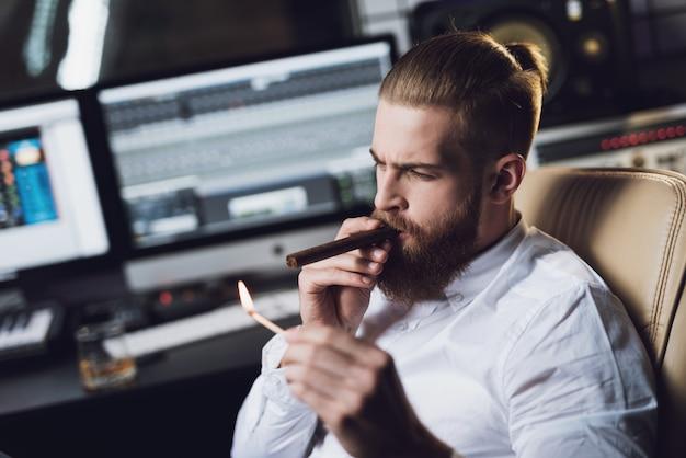 De mannelijke producent zit in de opname en rookt.