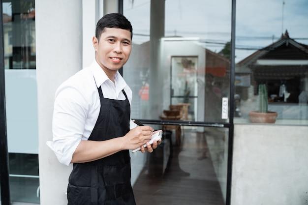 De mannelijke serveerster die van de koffie zich houdt met houdt een pen en een nota