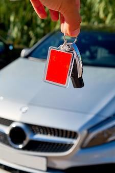 De mannelijke sleutels van de holdingsauto met auto op achtergrond.
