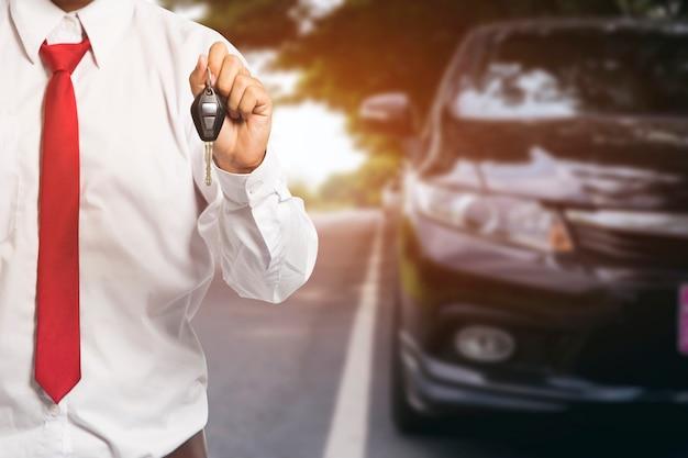 De mannelijke sleutels van de holdingsauto met auto op achtergrond