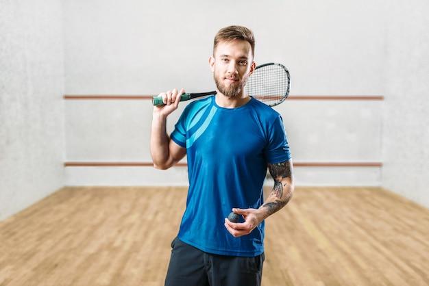 De mannelijke speler van het squashspel met racket en bal in handen