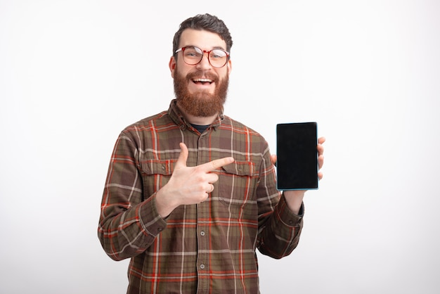 De mannelijke student richt op het leeg scherm van een tablet op witte achtergrond.