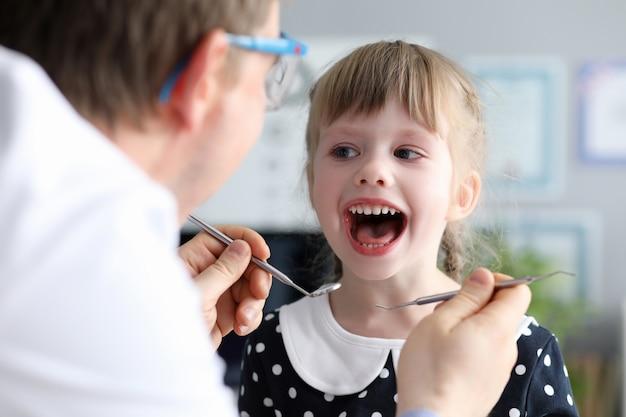 De mannelijke tandarts bekijkt open meisje weinig gelukkig meisje