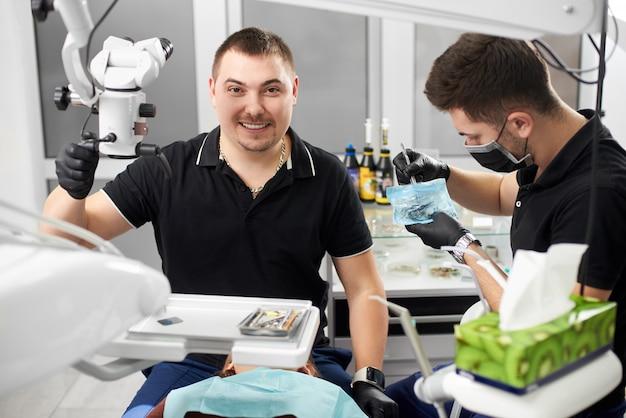 De mannelijke tandarts met ceramische steunen glimlacht terwijl een andere met medische instrumenten werkt