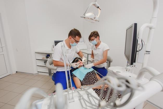 De mannelijke tandarts met een vrouwelijke assistent helpt de tanden van een vrouwelijke patiënt te behandelen in een kliniek op kantoor in