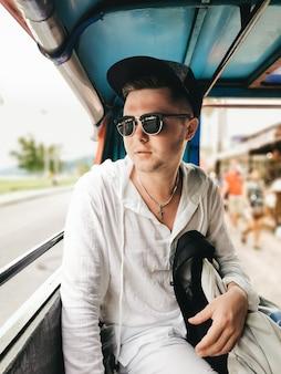 De mannelijke toerist berijdt een tuktuktaxi, phuket, thailand