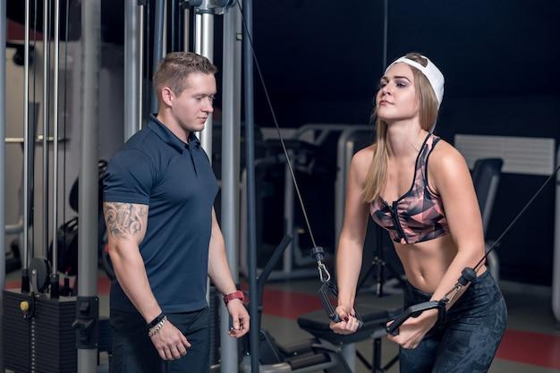 De mannelijke trainer helpt jonge geschiktheidsvrouw oefening met oefening-machine kabeloversteekplaats in gymnastiek uitvoeren