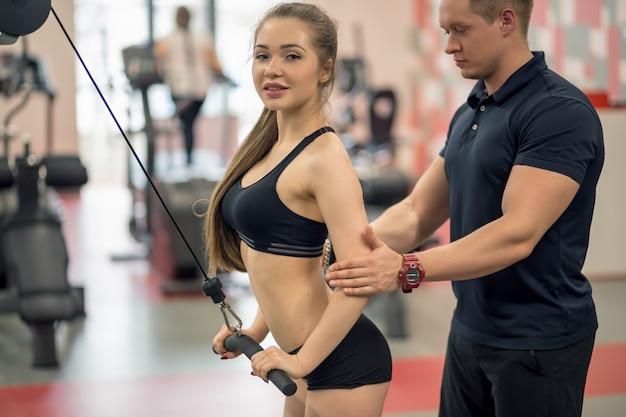 De mannelijke trainer helpt jonge geschiktheidsvrouw oefening met oefening-machine kabeloversteekplaats uitvoeren in gymnastiek, horizontale foto