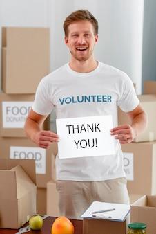 De mannelijke vrijwilliger van smiley bedankt je voor het doneren van voedsel