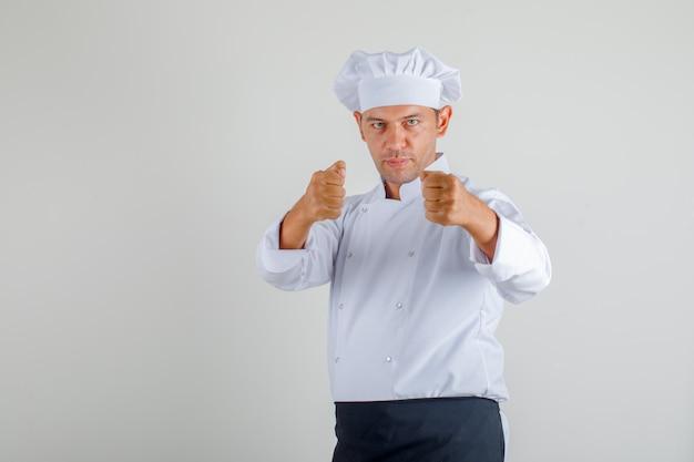 De mannelijke vuist van het chef-kokponsen om in uniform, schort en hoed te vechten en agressief het kijken. vooraanzicht.