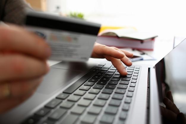 De mannelijke wapens houden creditcarddrukknopen die overdrachtclose-up maken. antifraude financiële beveiliging bij het invoeren van klantkortingsprogrammanummer of het invullen van persoonlijke inloggegevens wachtwoord login op account