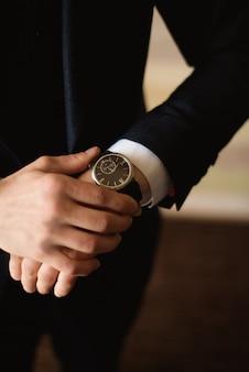 De mannelijke zakenman kleedt zich en past zijn horloge aan, voorbereidingen treffend voor een vergadering. klok