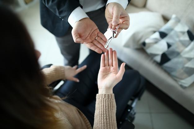 De mannelijke zakenmanhand geeft de sleutel door aan een vrouw van nieuwe huisvesting