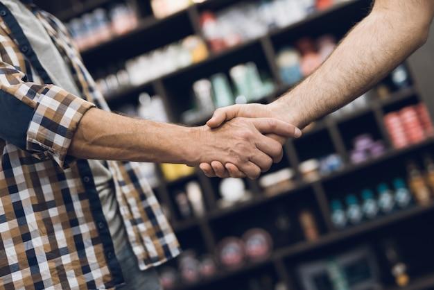 De mannen begroeten elkaar en schudden elkaar de hand.