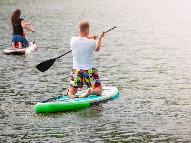 De mannen en vrouwen met haar baby staan paddle-boarding sup
