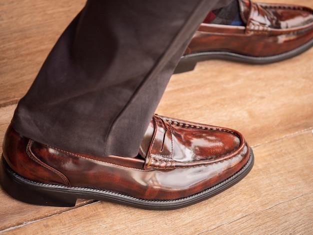 De mannen mannequin draagt de grijze broek en bruine schoenen leer op houten vloer. man collectie concept.