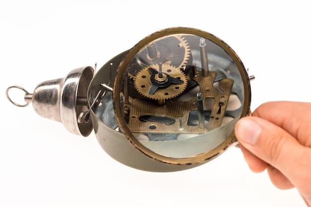 De mannenhand met vergrootglas en uurwerk