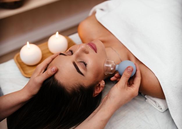 De massagetherapeut die van het meisje hoofdmassage doet mooi donkerbruin meisje.