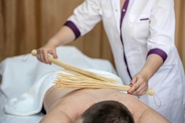 De masseur geeft een japanse massage aan een man met bamboe bezems.