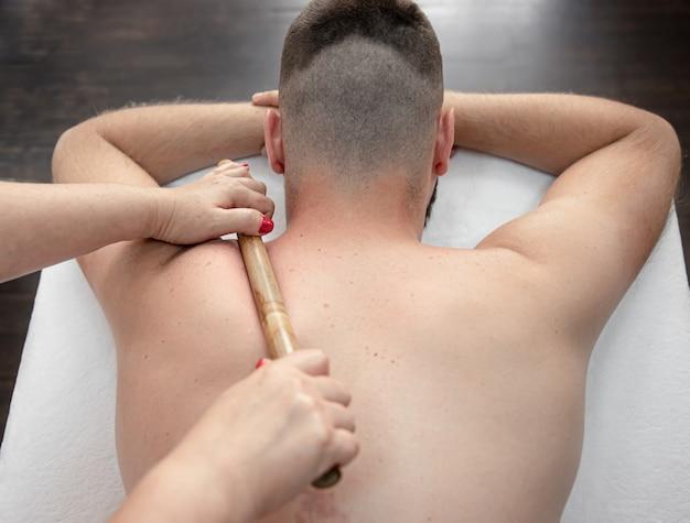 De masseur masseert bamboestokken tijdens de behandeling.
