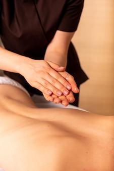 De masseuse wrijft voor de massage haar handen in met olie