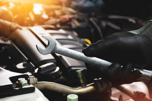 De mechanische hand die zwarte handschoenen draagt die een steeksleutel met een vaag zonlicht en een motor houden
