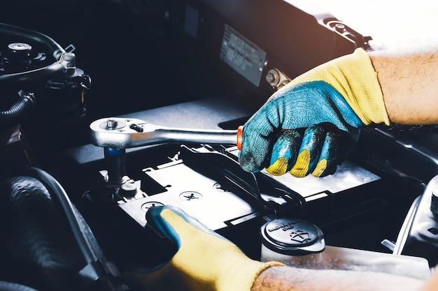 De mechanische hand is zet de bout van batterij anode met dopsleutel vast;