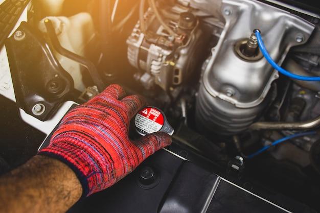 De mechanische mens met rode handschoen opent radiator glb van een auto, automobielonderhoudsconcept.