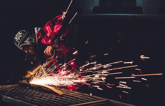 De medewerker van het servicestation produceert carrosseriereparatie met een lasapparaat in de hand