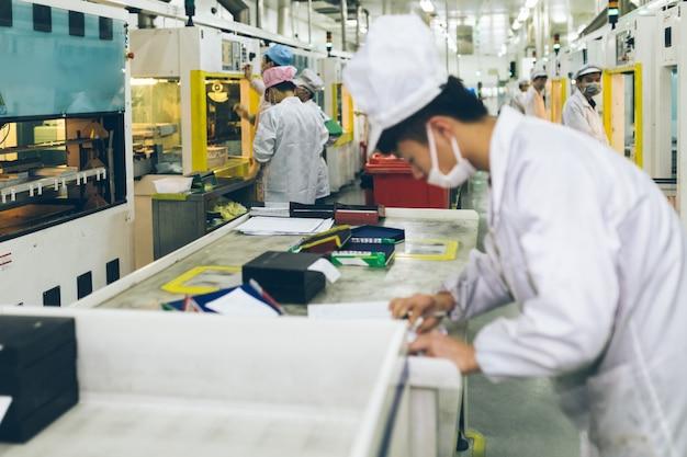 De medewerkers van het witte laboratoriumkostuum werken in de fabriek