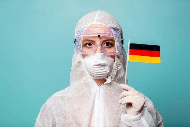 De medicvrouw die beschermende kleding draagt tegen het virus houdt de vlag van duitsland