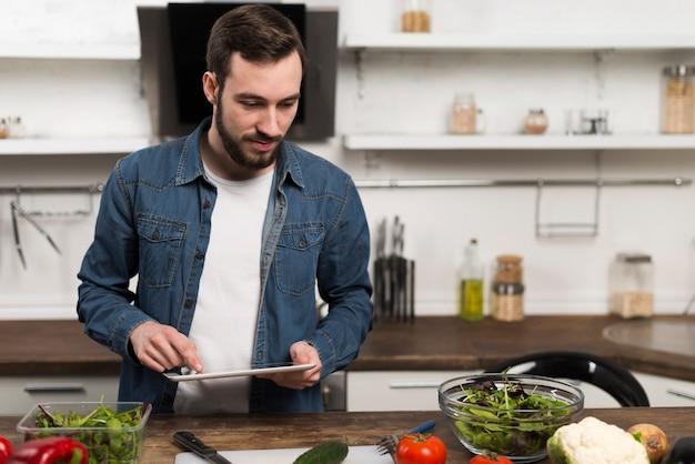 De medio geschotene tablet van de mensenholding in keuken