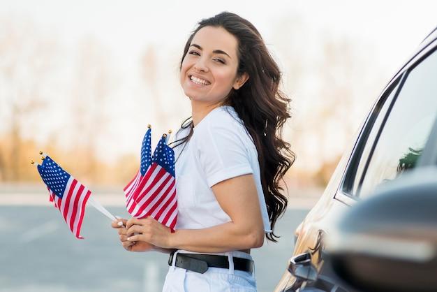 De medio geschotene vlaggen van de vs van de vrouwenholding dichtbij auto
