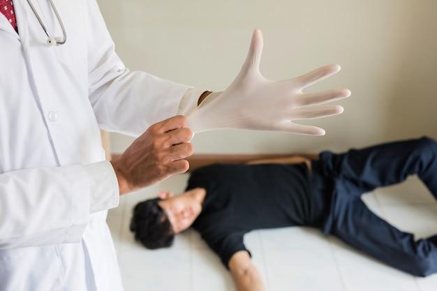 De medische examinator draagt handschoen aan autopsie