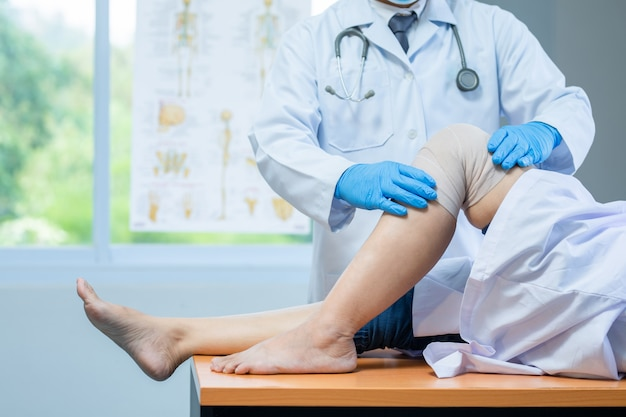 De medische handschoenen van de close-uphand dragen arts die hoofd van patiënt met knieproblemen onderzoeken in kliniek.