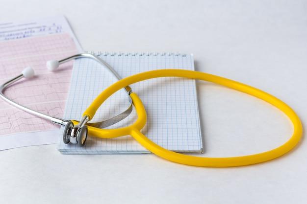 De medische stethoscoop op cardiogramgrafiek met een blocnote, sluit omhoog.