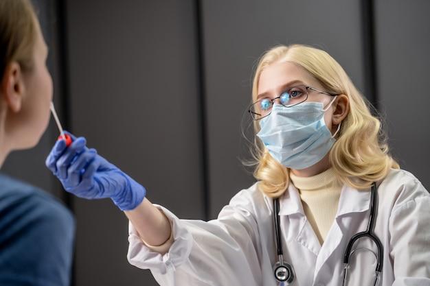 De medische werker neemt een monster voor analyse van een persoon om te testen op mogelijke coronavirusinfectie
