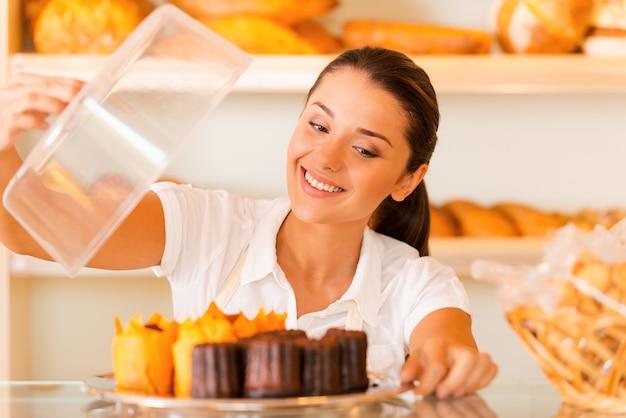De meest verse bakkerij voor onze klanten. mooie jonge vrouw in schort met bord met verse koekjes en glimlachend terwijl ze in de bakkerij staat