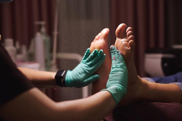 De meester brengt een voetscrub aan op de benen van de vrouw en masseert ze tijdens het maken van een pedicure in de schoonheidssalon