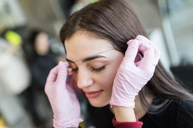 De meester controleert de contouren van vrouwelijke modelwenkbrauwen