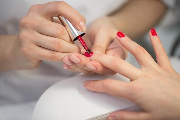 De meester die van de vrouwenspijker spijkers doen aan een meisjescliënt bij een schoonheidssalon. schoonheidsspecialiste brengt rode nagellak op de nagels van een jonge vrouw