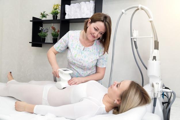 De meester in de schoonheidssalon maakt een lpg-massage.