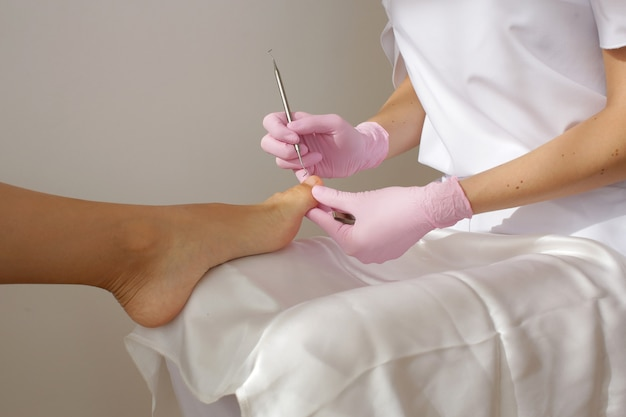 De meester in roze handschoenen maakt een pedicure op het been van de vrouw. hoge kwaliteit foto