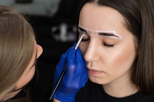 De meester maakt de procedure voor wenkbrauwcorrectie voor een jong meisje.