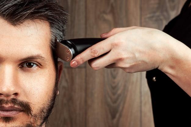 De meester maakt een knipbeurt naar de klant met een elektrische machine, trimmer, close-up. het proces van mannelijke kapsels bij de kapper, herenkapper. lichaamsverzorging, levensstijl, metroseksueel.