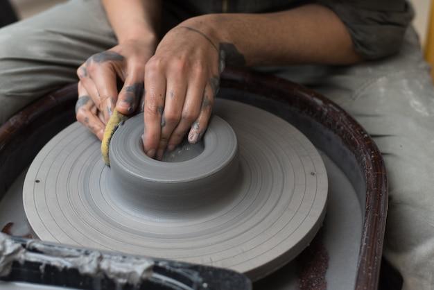 De meester maakt producten van grijze klei op een pottenbakkerswiel. meisje maakt een keramische vaas