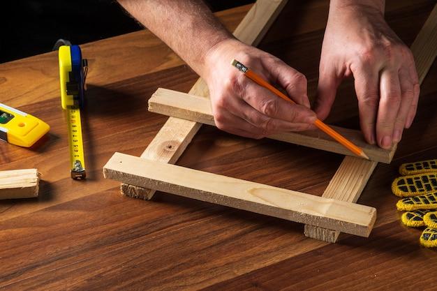 De meester markeert de afstand op de houten plank met een potlood.