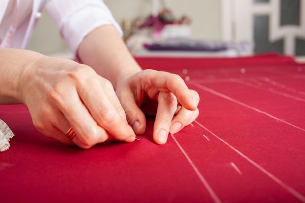 De meester-naaister schommelt twee delen van de stof met spelden.