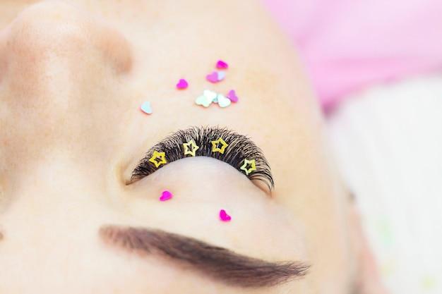 De meester van wimperverlenging versiert de wimpers van het meisje met strass-steentjes, hartjes en sterren. creatieve wimperextensions, oogmake-up.